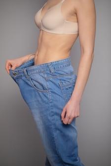 Koncepcja odchudzania. młoda kobieta pokazuje jej utrata masy ciała i nosi stare dżinsy. szczupła kobieta w dużych dżinsach, pokazując, jak schudła