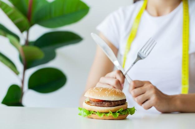 Koncepcja odchudzania, młoda kobieta z zamkniętymi ustami, rezygnując z fast foodów.
