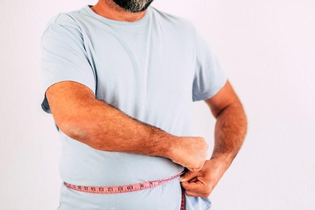 Koncepcja odchudzania z nierozpoznawalnym kaukaskim mężczyzną biorącym i sprawdzającym rozmiar brzucha za pomocą narzędzia cali - zdrowy styl życia i dieta