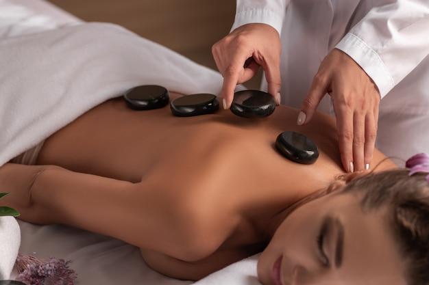 Koncepcja odnowy biologicznej, piękna i relaksu - piękna młoda kobieta o masaż gorącymi kamieniami w spa