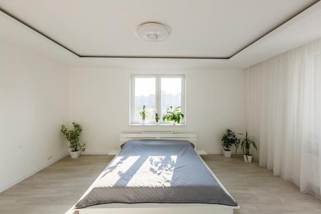 Koncepcja odpoczynku, wnętrza, komfortu i pościeli - łóżko w sypialni domu