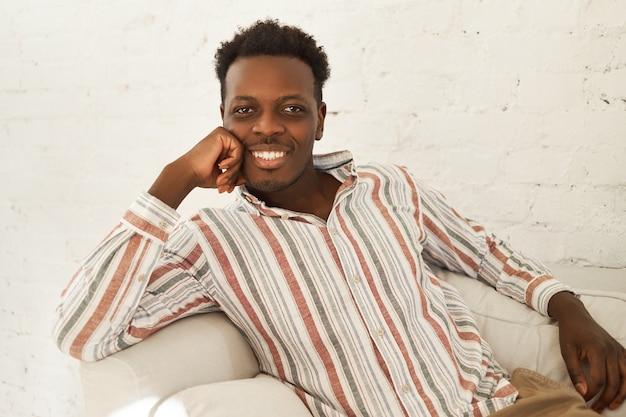 Koncepcja odpoczynku, wypoczynku i relaksu. fajny, charyzmatyczny młody afroamerykanin w codziennym ubraniu relaksujący się w domu