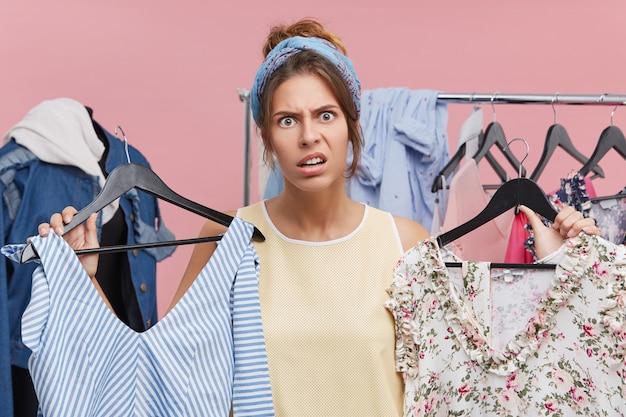 Koncepcja odzieży, mody, stylu i ludzi. zestresowana młoda europejka ma niezdecydowany i sfrustrowany wygląd podczas wybierania sukienki na imprezę, ale nie może znaleźć dla niej nic odpowiedniego