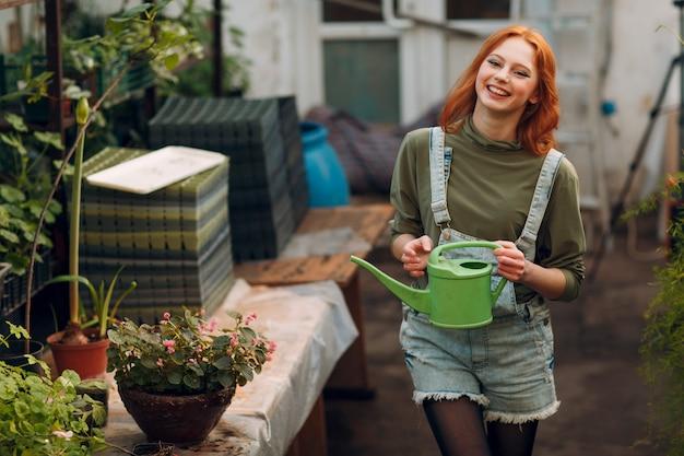 Koncepcja ogrodnictwa domowego. młodego agronomu uśmiechnięta kobieta z podlewanie puszki sadzenia roślinami. wiosenna przydomowa roślina ogrodowa.