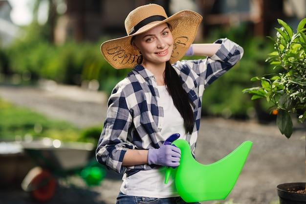 Koncepcja ogrodnictwa. portret piękne kobiece ogrodnik podlewania roślin w ogrodzie w upalny letni dzień.
