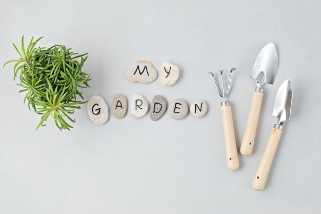 Koncepcja ogrodnictwa w domu. mieszkanie leżało z tekstem mój ogród na kamieniach i narzędziach ogrodniczych. minimalna kompozycja widoku z góry