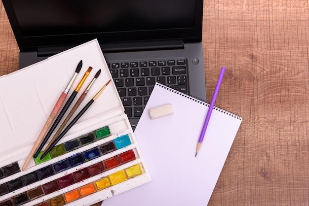 Koncepcja okładki klasy rysunku online z laptopem, kartką papieru, farbami i pędzlami na drewnianym biurku. edukacja online. powrót do makiety szkoły.