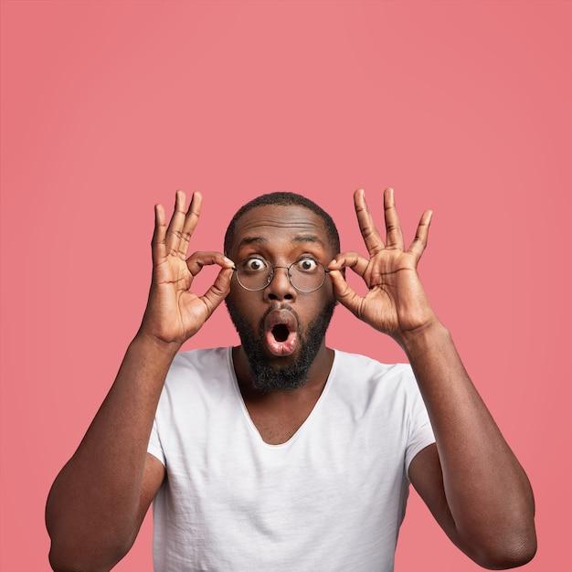 Koncepcja omg. african american mężczyzna patrzy w kamerę z zaskoczeniem