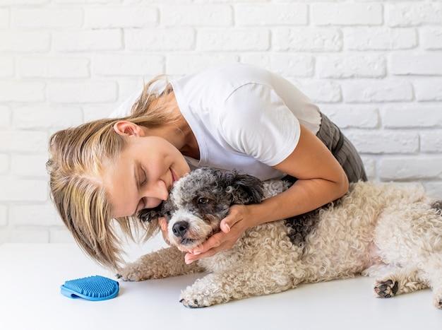 Koncepcja opieki nad zwierzętami. młoda blond kobieta przytulanie psa rasy mieszanej