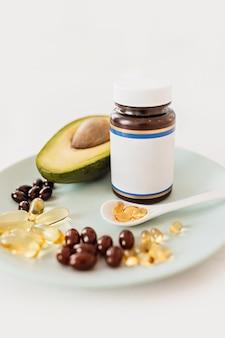 Koncepcja opieki zdrowotnej i diety. awokado i olej rybny w kapsułkach na witaminę d i kwasy tłuszczowe omega-3 w talerzu na białym tle