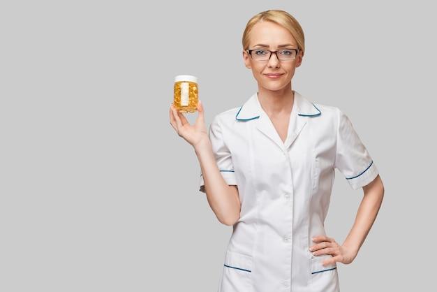 Koncepcja opieki zdrowotnej i diety - lekarz dietetyk lub kardiolog trzymający olej rybny w kapsułkach na witaminę d i kwasy tłuszczowe omega-3