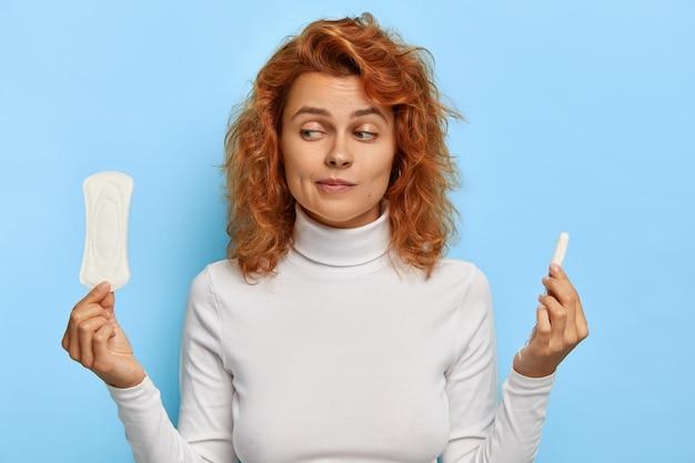 Koncepcja opieki zdrowotnej i higieny kobiet. ujęcie w pomieszczeniu niepewnej młodej rudej kobiety trzymającej dwa produkty intymne, podczas miesiączki wybiera tampon i podpaskę, zastanawia się, co daje lepszą ochronę