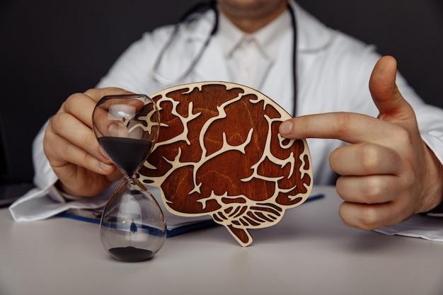 Koncepcja opieki zdrowotnej i leczenia. lekarz pokazuje drewniany mózg w swoim gabinecie.