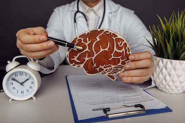 Koncepcja opieki zdrowotnej i leczenia mężczyzna lekarz pokazuje drewniany mózg