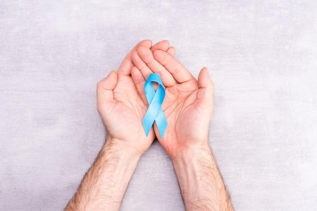 Koncepcja opieki zdrowotnej i medycyny - niebieska wstążka świadomości raka prostaty w męskich rękach, achalazji i raka kory nadnerczy