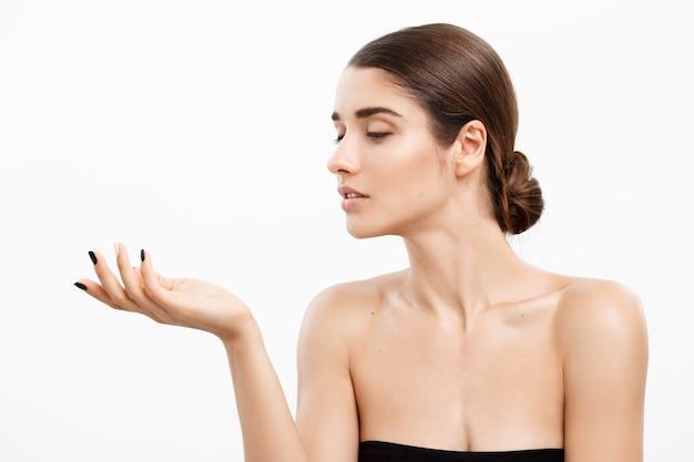 Koncepcja opieki zdrowotnej i spa - atrakcyjna młoda i zdrowa kobieta dmuchanie buziaka z jej ręki biała ściana.