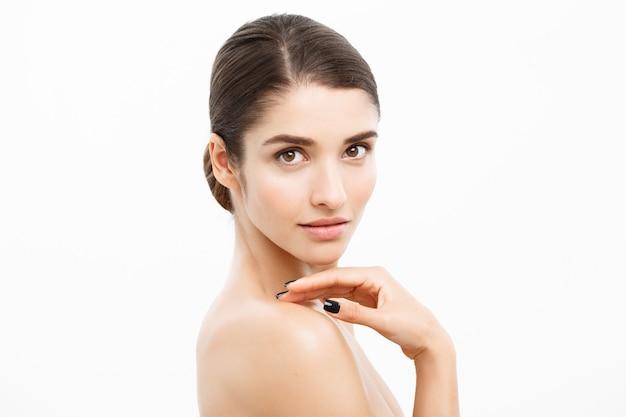 Koncepcja opieki zdrowotnej i spa - atrakcyjna młoda i zdrowa kobieta z nagim makijażem na białej ścianie.