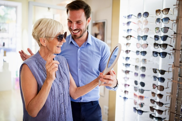 Koncepcja opieki zdrowotnej, ludzie, wzrok i wizja. starsza kobieta z mężczyzną optyk wybierający okulary w sklepie optycznym
