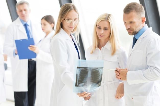 Koncepcja opieki zdrowotnej, medycznej i radiologii - grupa lekarzy patrząc na prześwietlenie