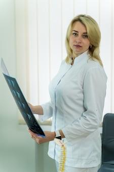 Koncepcja opieki zdrowotnej, medycznej i radiologii. lekarz patrzy na aparat rentgenowski w ręce.