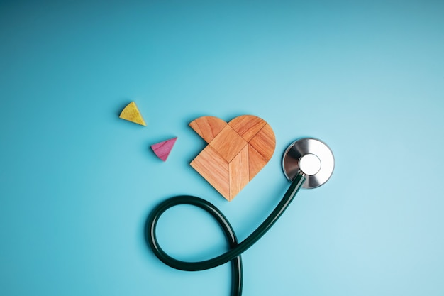 Koncepcja opieki zdrowotnej. międzynarodowy światowy dzień serca. drewniana wyrzynarka w kształcie serca ze stetoskopem