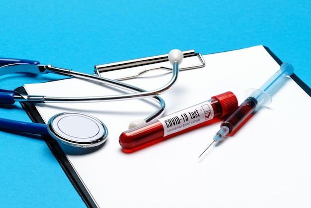Koncepcja opieki zdrowotnej - negatywna probówka do badania krwi covid-19, stetoskop, strzykawka i schowek z