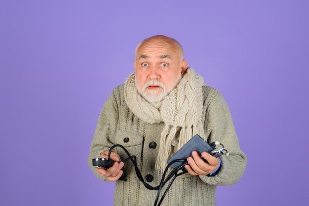 Koncepcja opieki zdrowotnej pomiar ciśnienia stary człowiek z ciśnieniem sfigmomanometru stary człowiek tętniczy