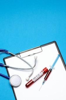 Koncepcja opieki zdrowotnej - pozytywna probówka do badania krwi covid-19, stetoskop, strzykawka i schowek z