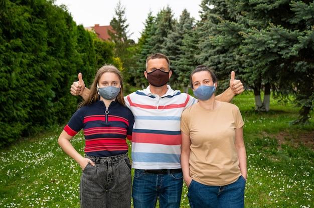 Koncepcja opieki zdrowotnej. rodzina w ochronnych maskach na twarz pozuje w parku