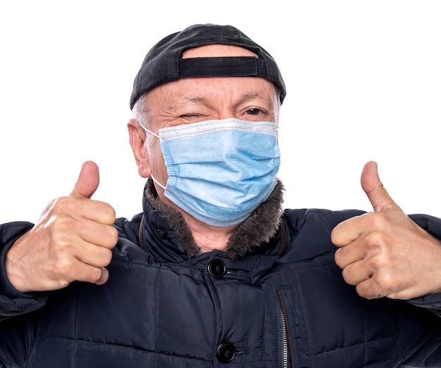 Koncepcja opieki zdrowotnej. starszy mężczyzna w masce ochronnej stwarzających w studio na białym tle. pokazuje znak ok