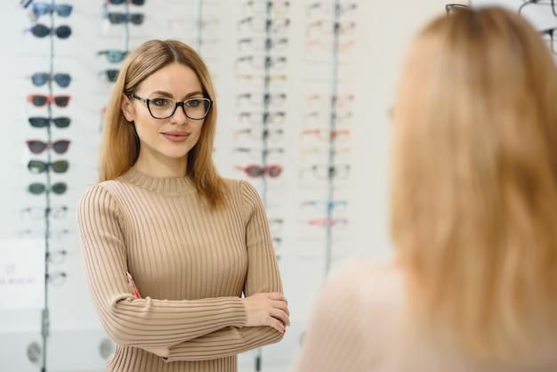 Koncepcja opieki zdrowotnej, wzroku i wzroku - szczęśliwa kobieta wybierając okulary w sklepie optycznym. portret piękna młoda kobieta próbuje nowych okularów w sklepie optyka