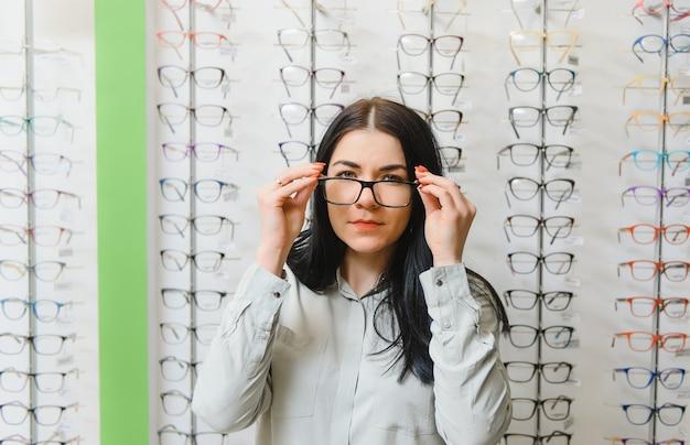 Koncepcja opieki zdrowotnej, wzroku i wzroku - szczęśliwa kobieta wybierająca okulary w sklepie optycznym
