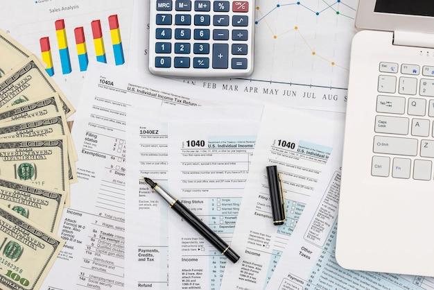 Koncepcja opodatkowania, wykresy biznesowe z banknotów dolara i laptopa