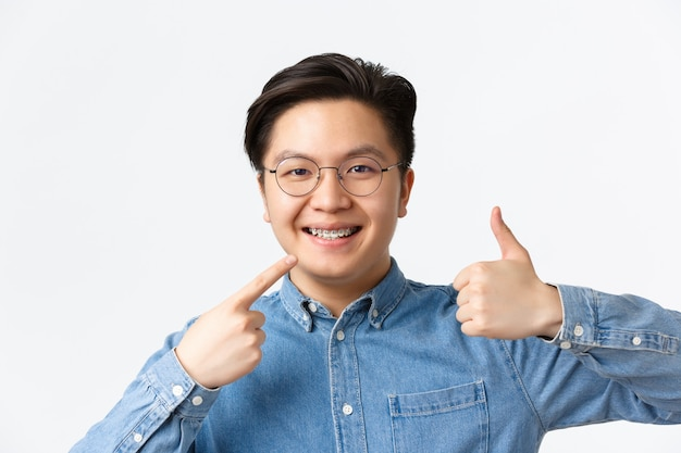 Koncepcja ortodoncji i stomatologii. zbliżenie na zadowolonego azjatę, klienta kliniki dentystycznej uśmiechniętego szczęśliwie, wskazującego na swój aparat ortodontyczny i pokazującego aprobatę kciuka w górę, polecam.