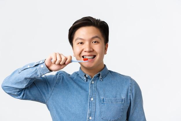 Koncepcja ortodoncji, opieki stomatologicznej i higieny. zbliżenie: przyjaźnie wyglądający uśmiechnięty azjatycki mężczyzna szczotkujący zęby aparatem ortodontycznym, trzymając szczoteczkę do zębów, stojąc na białej ścianie