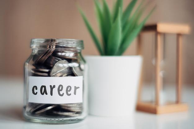 Koncepcja oszczędności dla kariery - szklany słoik z monetami i napisem.