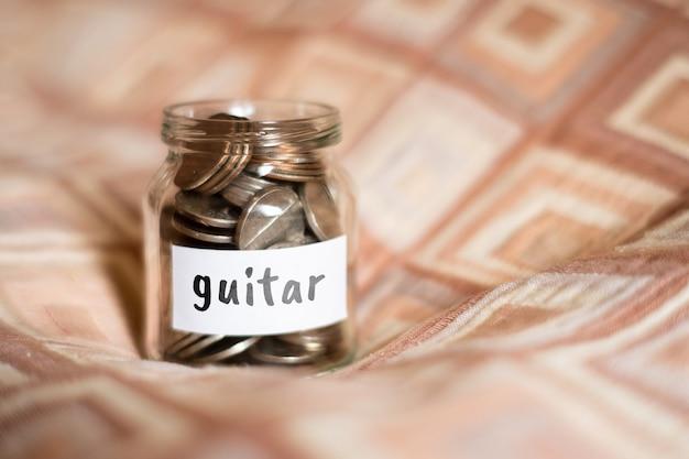 Koncepcja oszczędności na gitarze - szklany słoik z monetami i napisem.