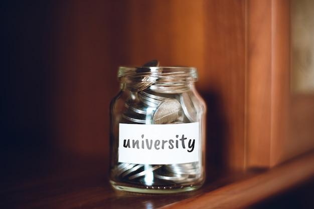 Koncepcja oszczędności uniwersyteckich - szklany słoik z monetami i napisem.