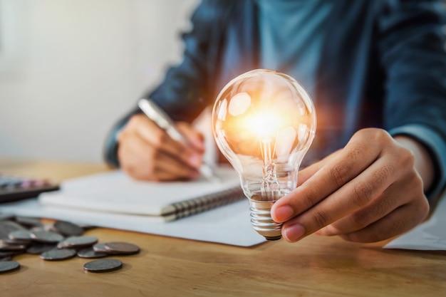 Koncepcja oszczędzania energii. bizneswoman gospodarstwa żarówki
