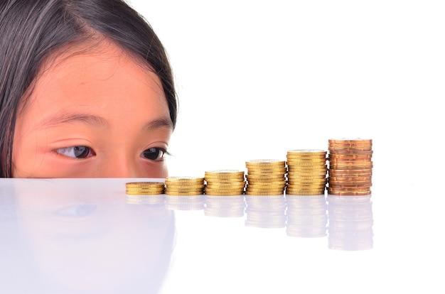 Koncepcja oszczędzania - młoda dziewczynka patrząca na stos monet