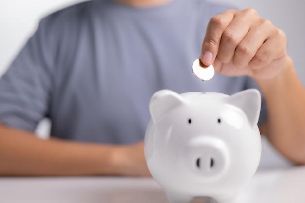 Koncepcja oszczędzania pieniędzy biznesmen ręka wkłada monetę do skarbonki