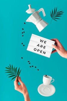"""Koncepcja otwartej kawiarni. modna lewitująca kawa i pączki. latająca linia ziaren kawy. ceramiczny ekspres do kawy, filiżanka espresso. lewitacja liścia palmowego, tablica """"jesteśmy otwarci"""". wibrująca zielona mięta"""