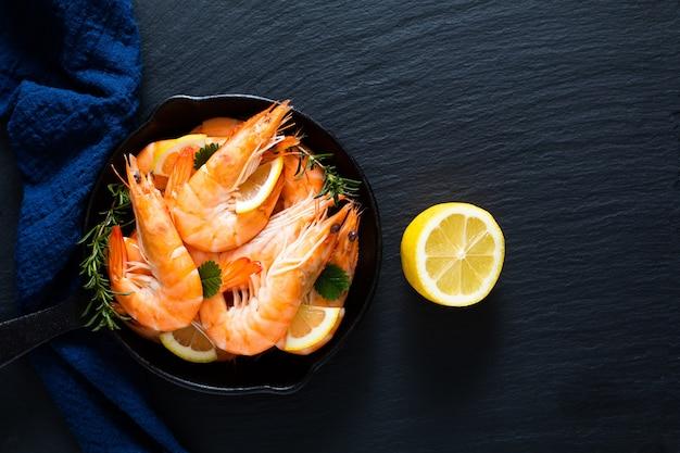 Koncepcja owoców morza krewetki króla oceanu gotowane na patelni żeliwnej odlanej na czarnym łupku z niebieskimi serwetkami