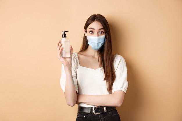 Koncepcja pandemii i opieki zdrowotnej. podekscytowana dziewczyna w masce pokazuje butelkę odkażacza do rąk, patrzy zdziwiona kamerą, stojąc na beżowym tle.