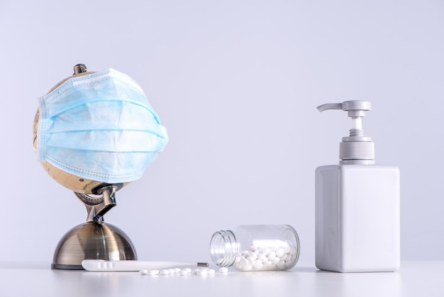 Koncepcja pandemii koronawirusa covid-19 na świecie. kula ziemska z maską na twarz, środkiem odkażającym, medycyną, termometrem klinicznym na białym tle