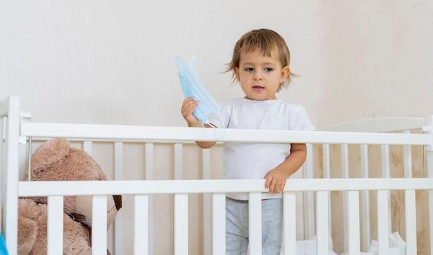 Koncepcja pandemii pandemii koronawirusa kwarantanny małe słodkie poważne dziecko jest w łóżeczku dziecięcym w domu w