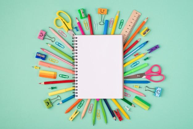 Koncepcja papeterii szkolnej. górne nad widokiem z góry zdjęcie kolorowej papeterii i pustego pustego otwartego notatnika w środku na białym tle na turkusowym tle