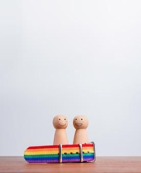 Koncepcja para lgbt. dwie drewniane figury ze szczęśliwym uśmiechem stoją razem w tęczowej flagi, opaska na stół z drewna i tło z miejsca na kopię, pionowy styl. symbol dumy lgbt.