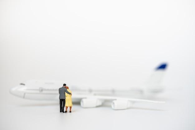 Koncepcja para, rodzina i podróże. mężczyzna i kobieta miniaturowe postacie ludzi przytulają się i chodzą do modelu mini samolotu