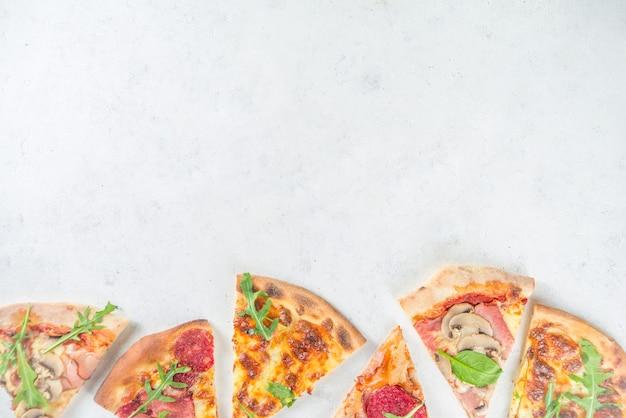 Koncepcja partii pizzy. zestaw pizzy z różnymi nadzieniami kawałki różnej pizzy, kieliszek i butelka z winem.